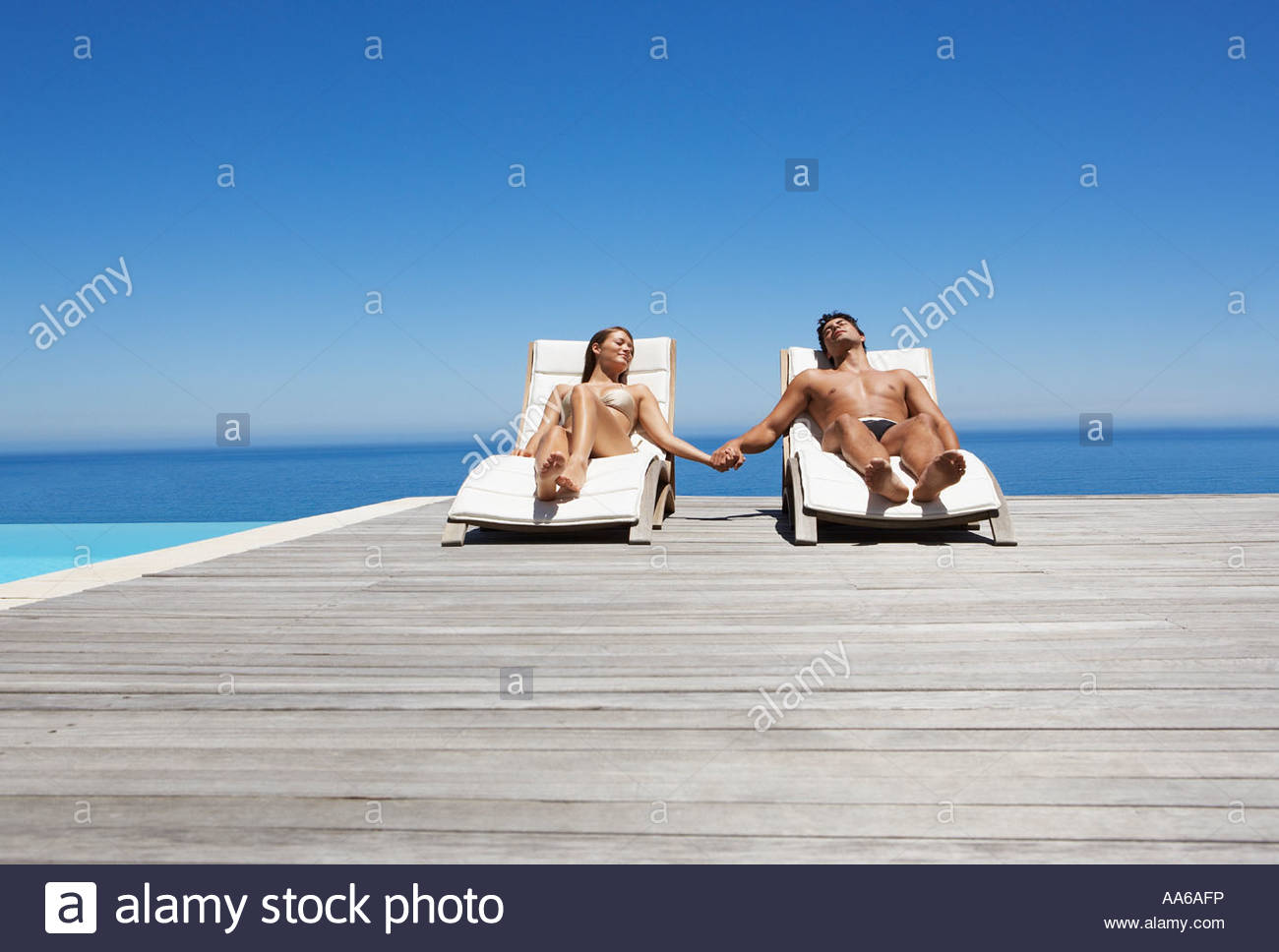 Sunbathing Chairs Man And Woman In Deck Chairs Sunbathing Holding Hands