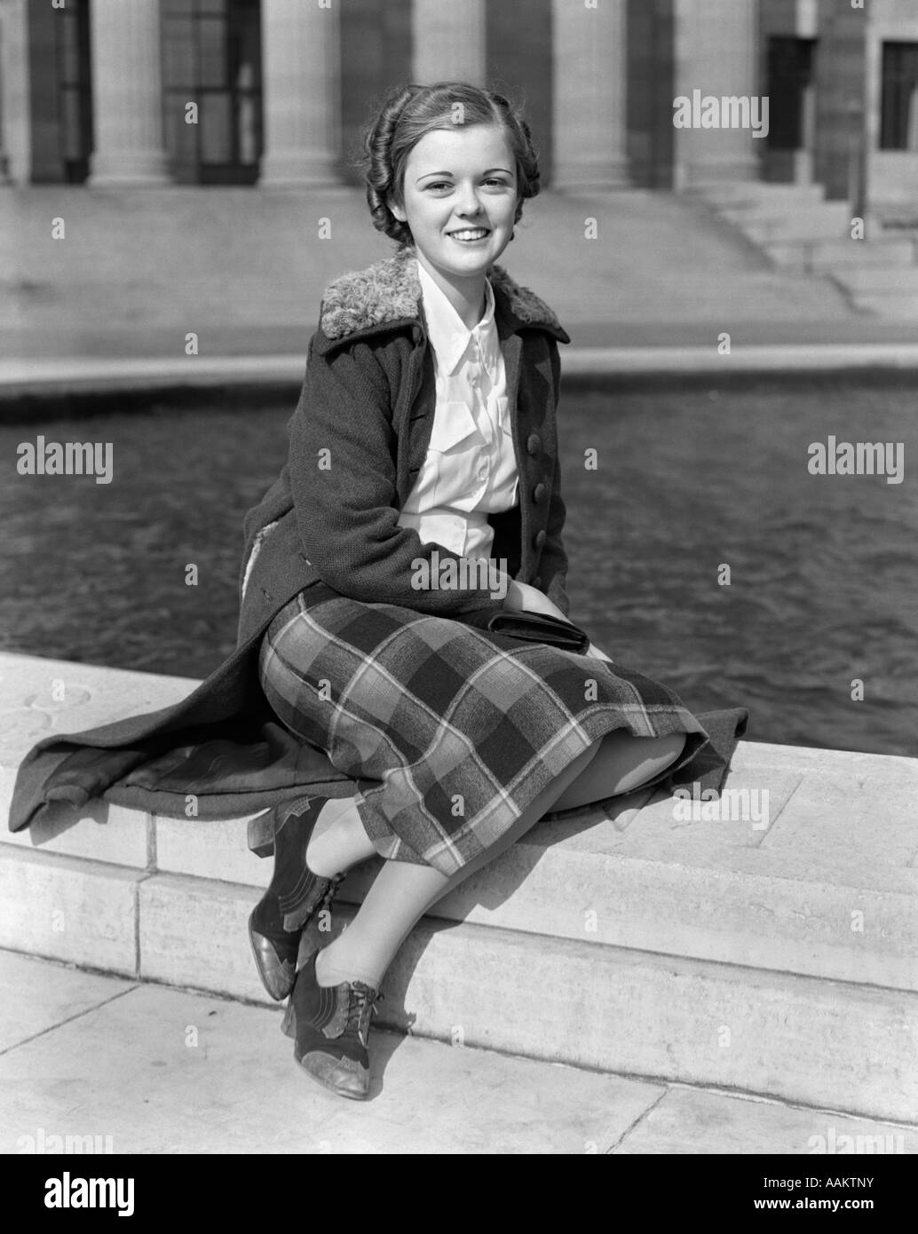 1930s SMILING TEEN GIRL SITTING AUTUMN CLOTHES Stock Photo