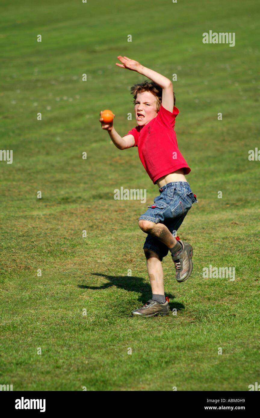 child throwing a ball outside stock photo