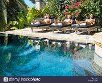 Three women sun tanning in lounge chairs by a pool Stock ...