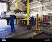 2 car mechanics working in a repair garage with hydraulic