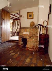 Old brick fireplace in the corner of cottage hall with ...