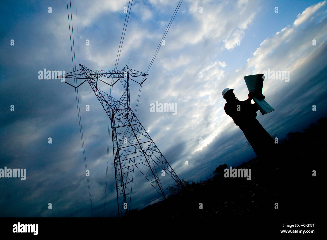 hight resolution of construction electrical worker studies plans beneath high voltage power lines stock image