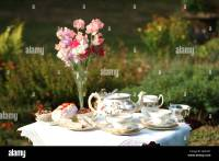 afternoon tea set on the lawn in English country garden ...