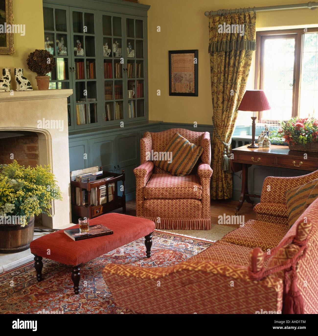 Patterned red sofa and armchair in livingroom with pale