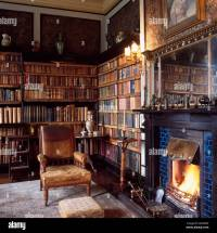 Edwardian leather armchair beside fireplace in study with ...