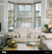 cream sofa in front of bay window with slatted blind in ...