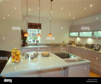 Pendant lights over island unit with halogen hob and ...