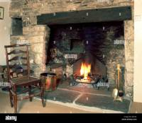 Fireside chair by old stone fireplace Stock Photo, Royalty ...