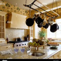 Kitchen Maid Champagne Bronze Faucet With Marble Top Surface And Saucepans Hung From Pulley