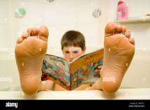 Young Boy With Feet In Warm Bath Reading Simpsons