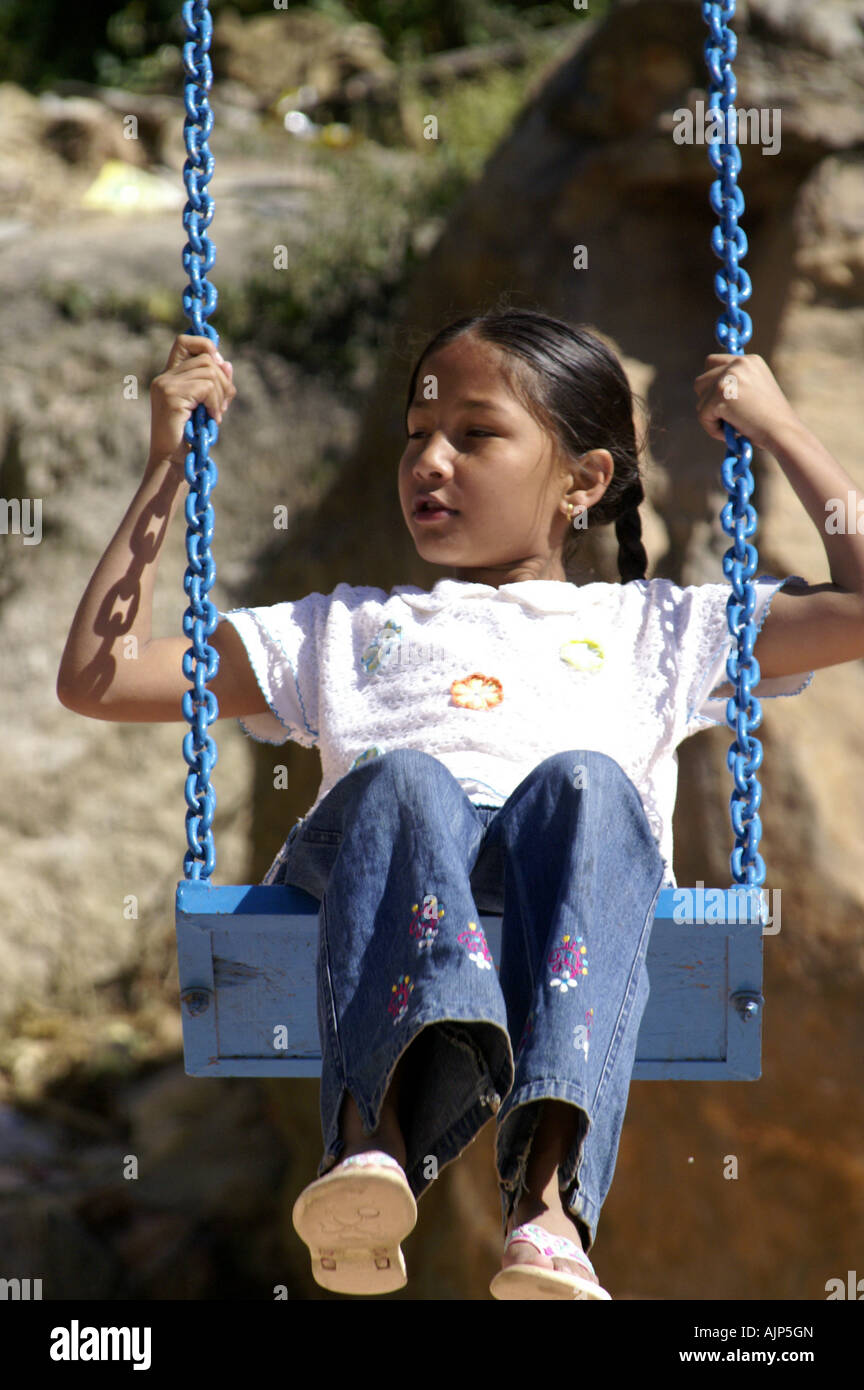 hight resolution of happy small young indian girl child playing sitting in harness of blue swing outdoors in india