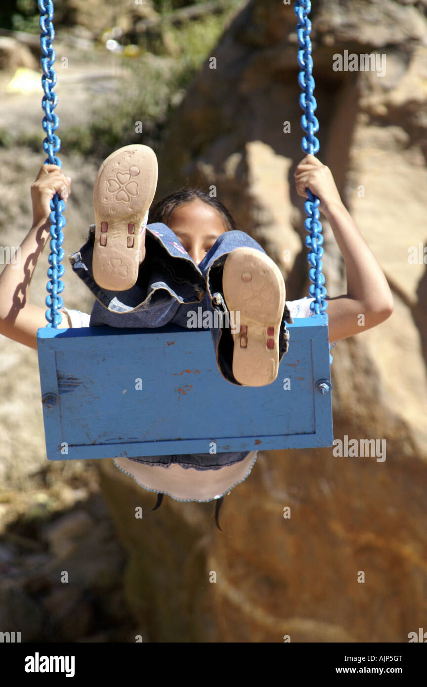 hight resolution of happy indian girl child sitting in swing harness playing outdoors in india