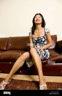 Korean Asian woman in formal dress sitting on leather sofa ...
