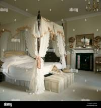 Silk edged white canopy and curtains on four poster bed ...