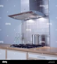 Stainless steel tiles below extractor fan above hob in ...