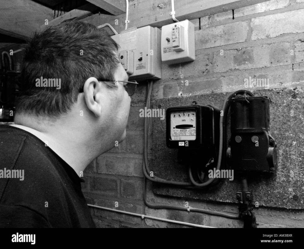 medium resolution of man reading and checking electric meter in garage