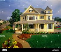 Large Two Story Yellow Victorian House With Blue Shutters