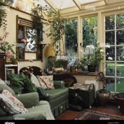 Traditional Armchairs For Living Room Storage Unit Comfy Green In Conservatory With Houseplants And View Of Garden Through Glass Door