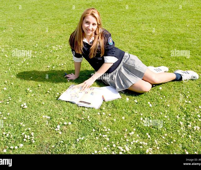 Teenage Blonde Schoolgirl With Her Books In The Park Laying On The Grass And Smiling