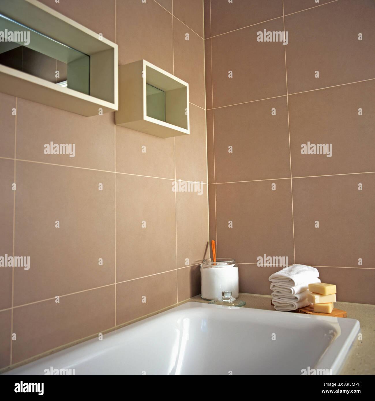 White Bath Below Mirrored Cube Shelves On Beige Tiled Walls