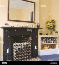Wine storage in fireplace below large mirror in pastel ...