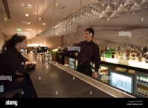 Barman Pours Drink In Contemporary Hotel Bar Stock