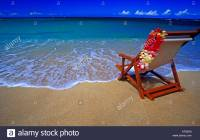 Beach chair draped with a colorful plumeria flower lei on ...