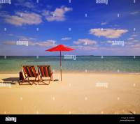 Tropical scene of two colorful beach chairs and an ...
