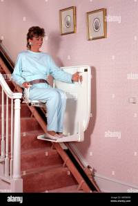 middle age aged woman female using stair chair lift ...
