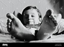 Little Boy Lying In Bed With Big Giant Feet Stock