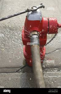 Leaking red fire hydrant and fire hose attached Stock ...