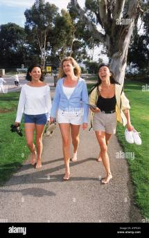 Three Women Of Ethnic Mix Walking Barefoot Park Pathway