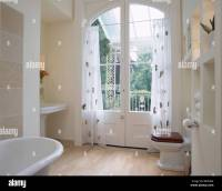 Patterned white voile curtains on French doors in modern ...