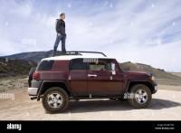 Man standing on roof rack of FJ Cruiser in desert Stock ...