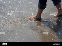 Woman With Painted Toenails And Rolled Jeans Splashes