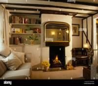 Large mirror above small fireplace in beamed cottage