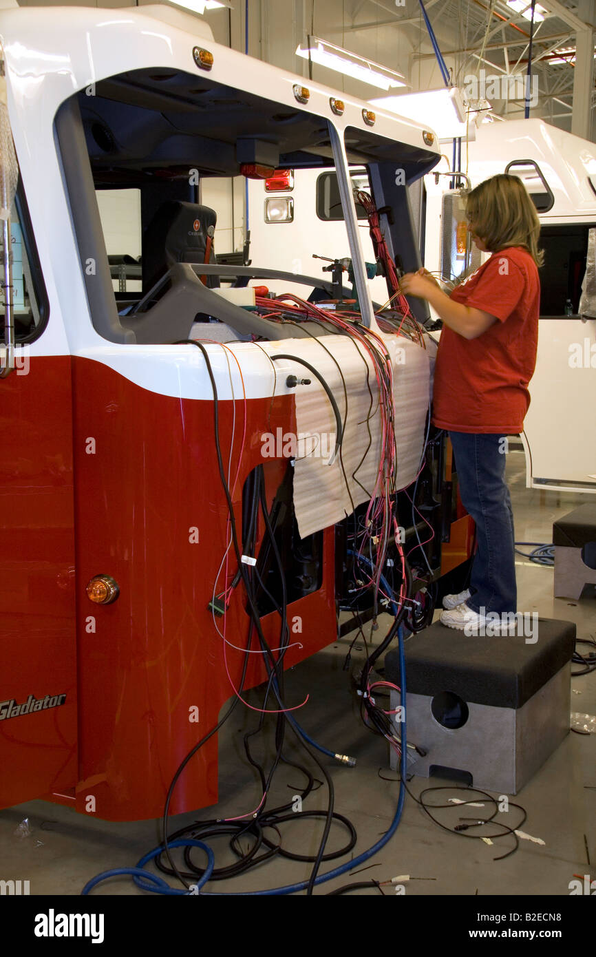 hight resolution of female worker installing wiring into a newly manufactured fire truck chassis at spartan motors in charlotte
