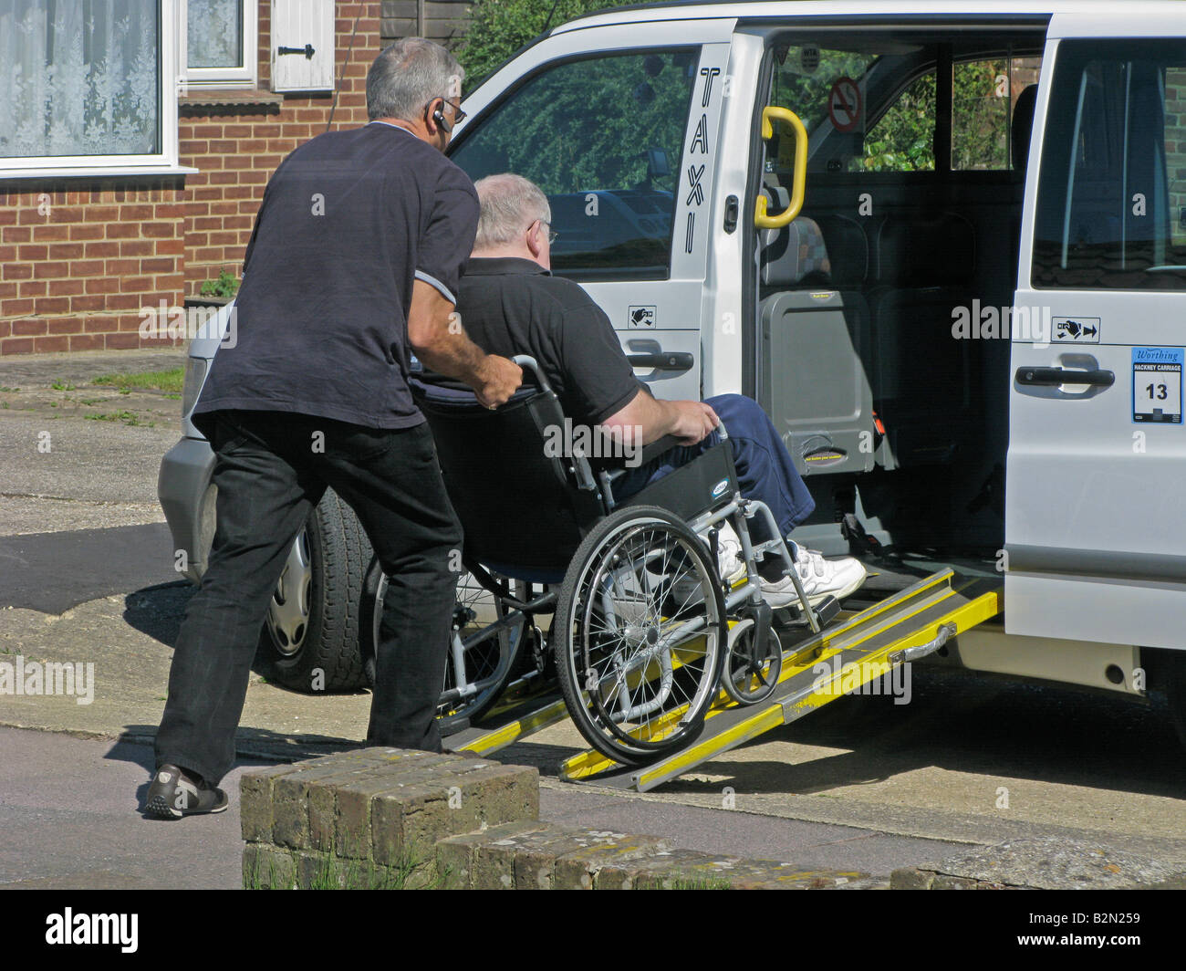 wheelchair cab table and chair rental taxi driver pushing an elderly disabled man from a ramp to