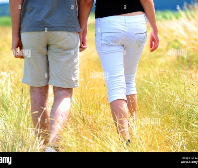 Teenagers Walking In A Field On A Hot Summers Day In Kent England Stock Image