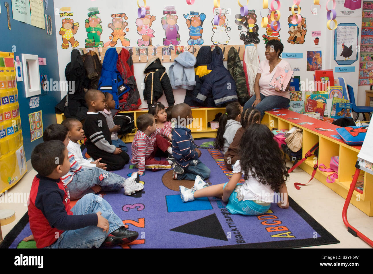 African American Preschool Teacher Reading A Book To Her
