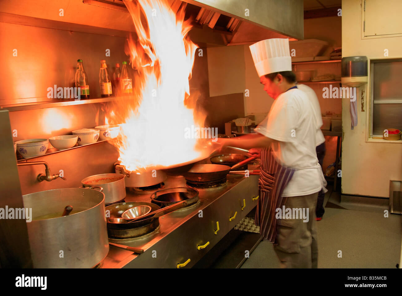 Male Thai Chef cooking with flaming wok in a restaurant