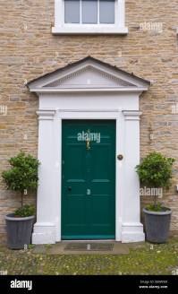 Green front door with white triangular pediment of ...