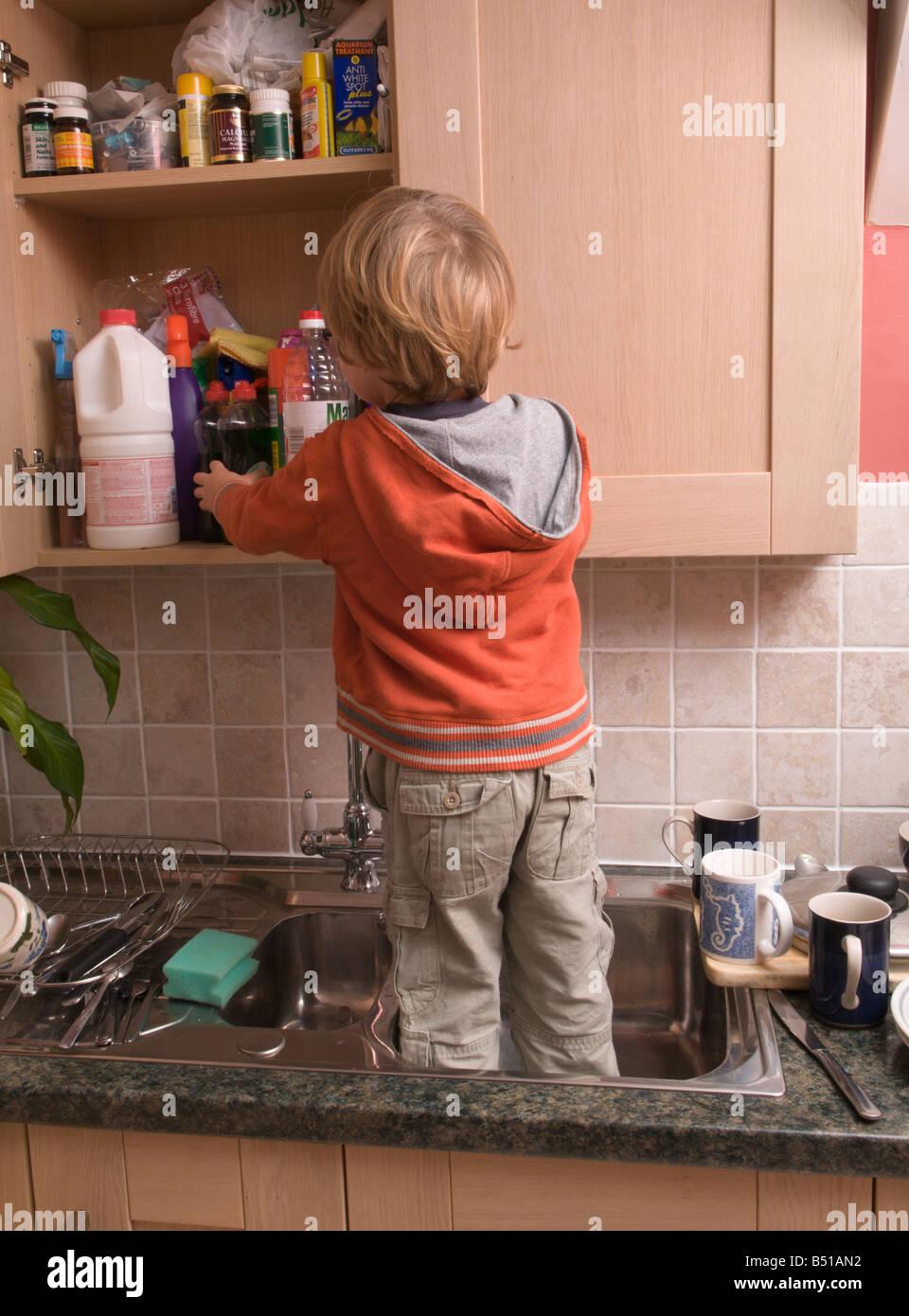 toddler boy child reaching dangerous kitchen cupboards by