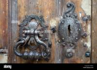 An ancient door knocker and lock on a battered old house ...