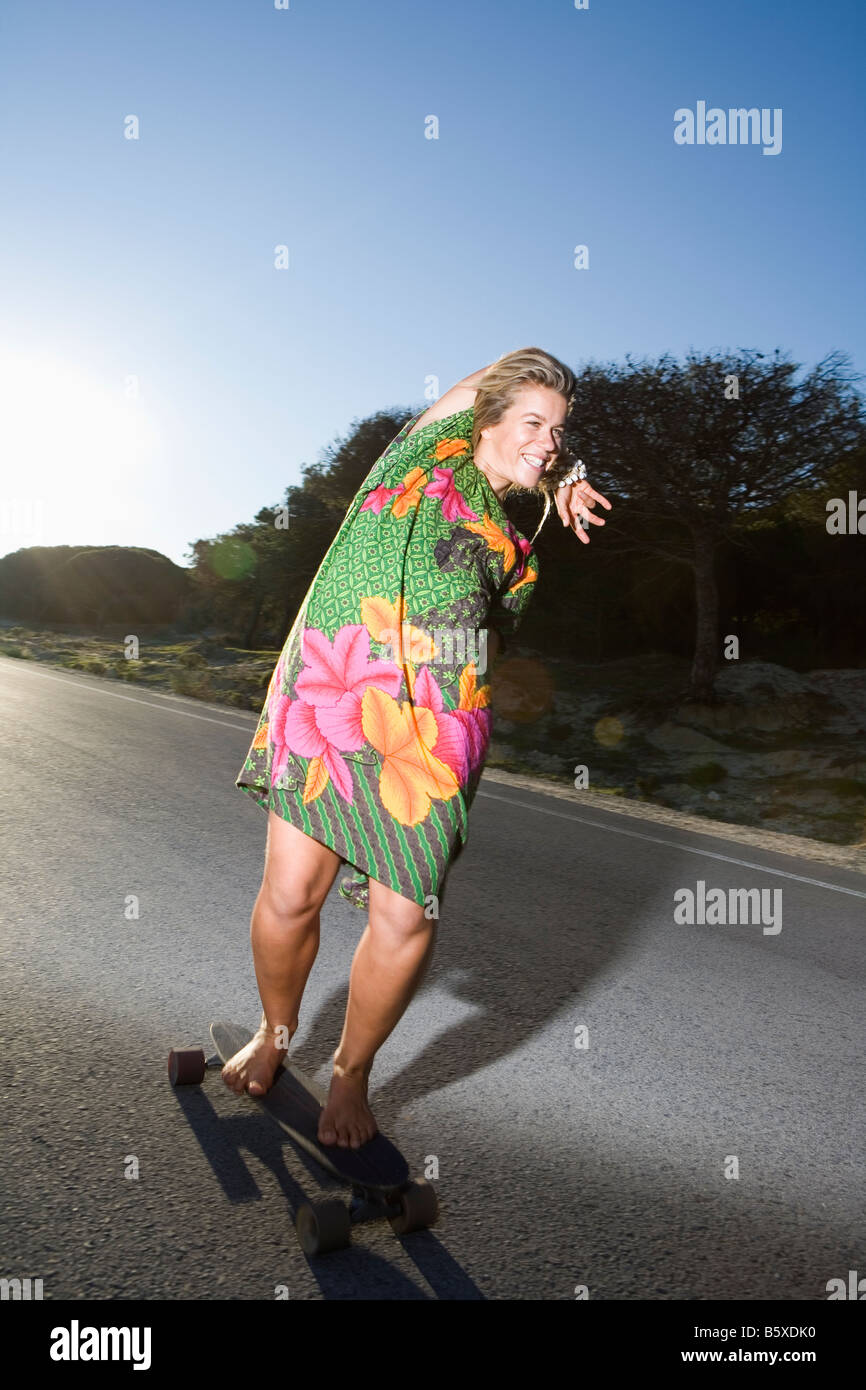 young woman skateboarding barefoot