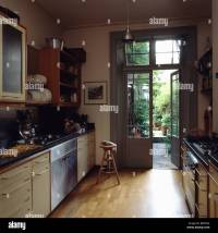 Wooden flooring in modern galley kitchen with French doors ...