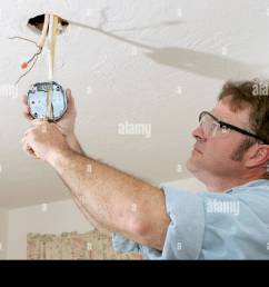 an electrician pulling wires through a ceiling fan box work is being performed to code by [ 1300 x 956 Pixel ]