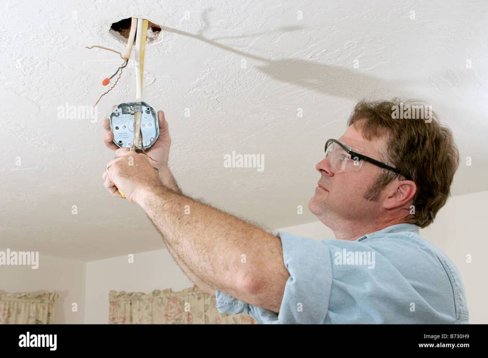 medium resolution of an electrician pulling wires through a ceiling fan box work is being performed to code by