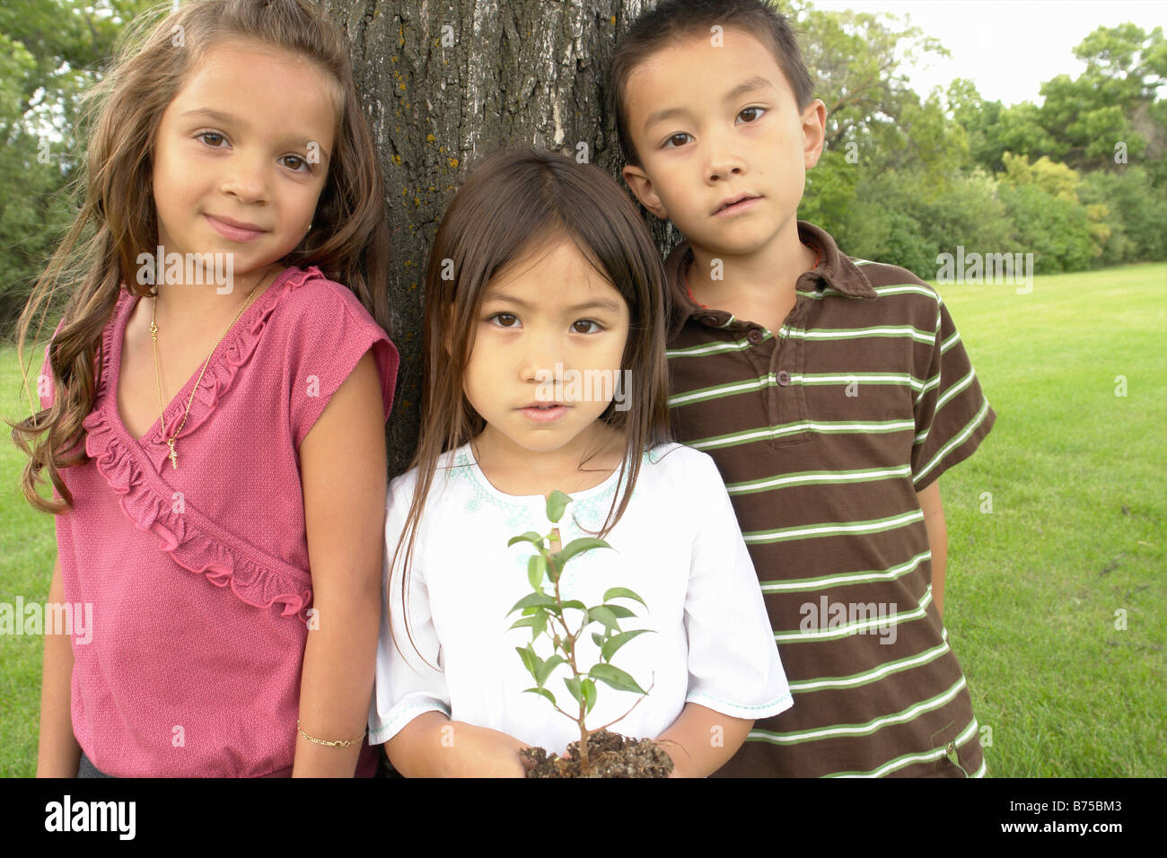 Five Year Old Girl Holds Small Tree Beside Seven Year Old